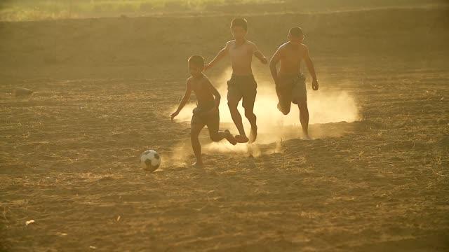 vídeos y material grabado en eventos de stock de lenta de los niños rurales está jugando fútbol en el día de sol en un pueblo. - países en vías de desarrollo