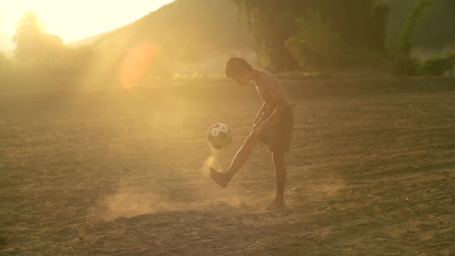 slow motion of rural children is playing football in the sunshine day in a village. - drive ball sports stock videos & royalty-free footage