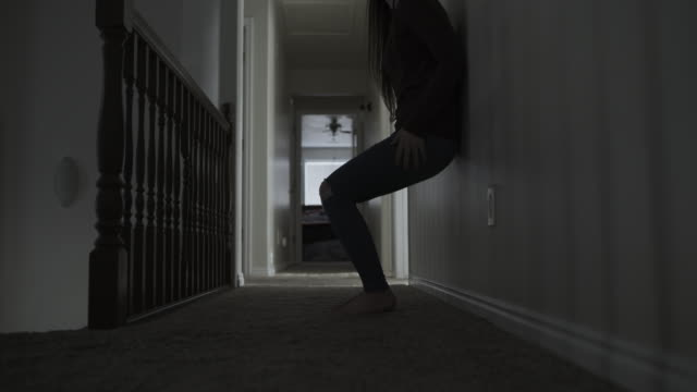 slow motion of sad girl walking in corridor then sitting on floor depressed / springville, utah, united states - full length stock videos & royalty-free footage