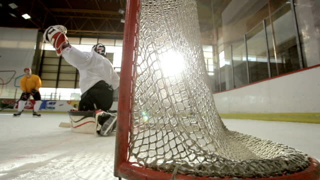 Slow motion of scoring a goal during ice hockey game at the arena.