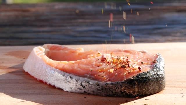 vidéos et rushes de mouvement lent de l'assaisonnement saupoudrant sur le poisson de saumon - goûter