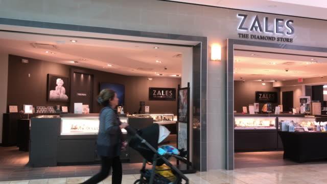 stockvideo's en b-roll-footage met slow motion of senior couple walking passing zales jewelry store inside a houston shopping mall - winkelbord