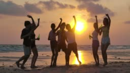 Slow motion of silhouette group of young people dancing at beach party on sunset.