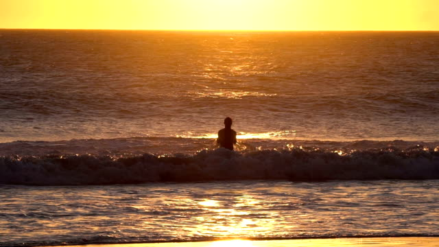 slow motion of silhouette of man jumping and playing with waves in the sea - silvestre stock videos & royalty-free footage