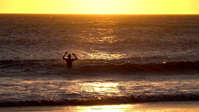 vídeos y material grabado en eventos de stock de slow motion of silhouette of man jumping and playing with waves in the sea - generosidad