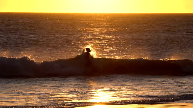 vídeos de stock e filmes b-roll de slow motion of silhouette of man jumping and playing with waves in the sea - nu