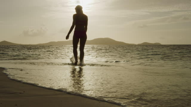 slow motion of silhouette of woman walking on beach into ocean at sunset / jamesby island, tobago cays, st. vincent and the grenadines - camminare nell'acqua video stock e b–roll