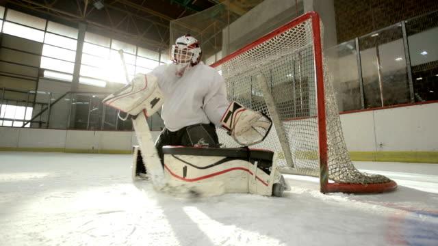 Slow motion of skillful ice hockey goaltender defending the goal.