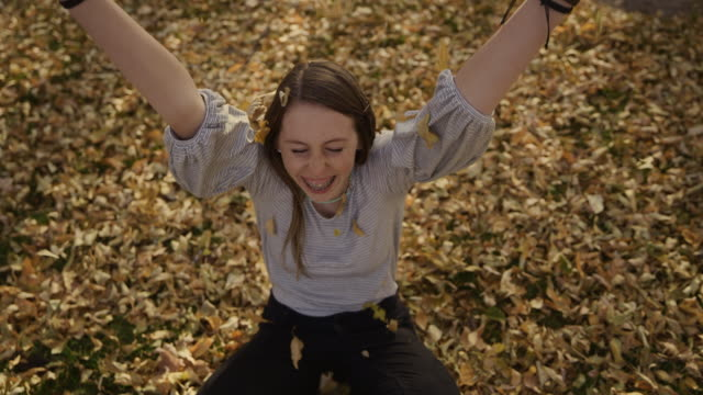 vídeos de stock, filmes e b-roll de slow motion of smiling girl throwing autumn leaves / cedar hills, utah, united states - plano americano