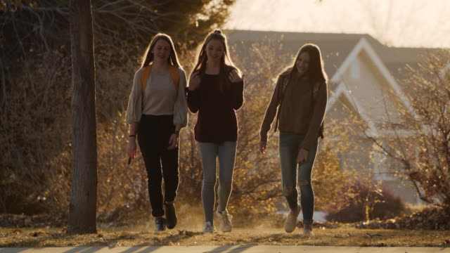 vídeos de stock, filmes e b-roll de slow motion of smiling girls wearing backpacks approaching and talking / cedar hills, utah, united states - plano americano