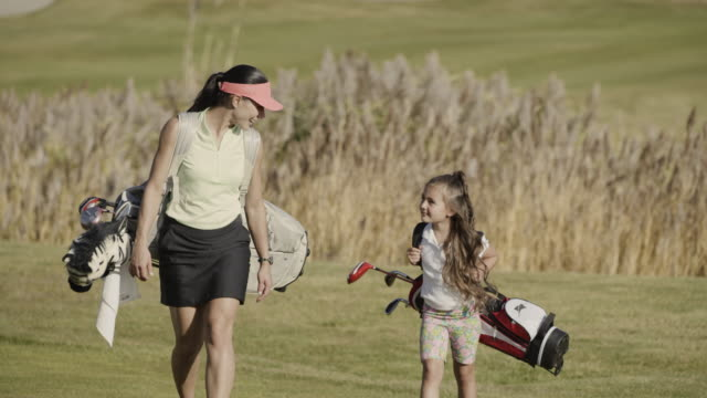 slow motion of smiling mother and daughter carrying golf bags on golf course / cedar hills, utah, united states - daughter stock videos & royalty-free footage