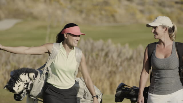 slow motion of smiling women carrying golf bags on golf course / cedar hills, utah, united states - golf course stock videos & royalty-free footage