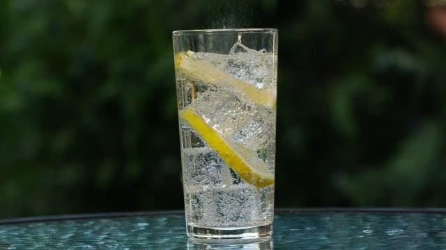 vidéos et rushes de mouvement lent de l'eau de soude avec des glaçons et le citron - hd format
