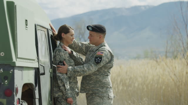 slow motion of soldier rejecting flirting from another soldier near military vehicle / lehi, utah, united states - oberkörperaufnahme stock-videos und b-roll-filmmaterial