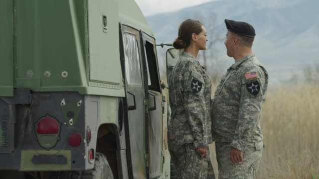 slow motion of soldiers kissing near military vehicle / lehi, utah, united states - 光栄点の映像素材/bロール