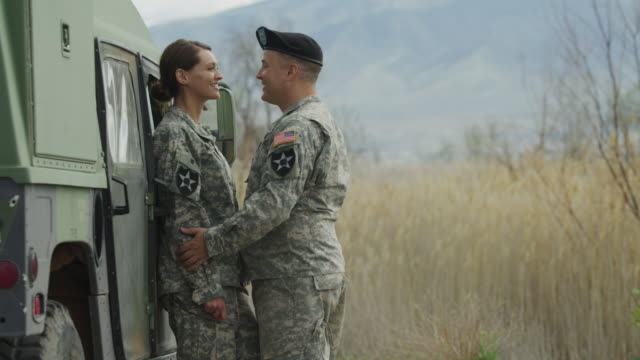 vídeos de stock e filmes b-roll de slow motion of soldiers kissing near military vehicle / lehi, utah, united states - tropa