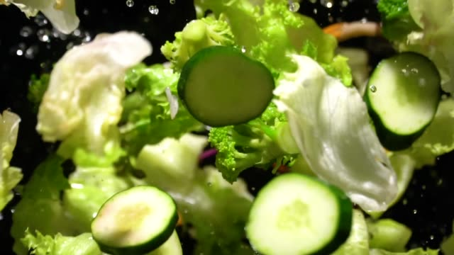 slow motion of splashing green salad flying up to camera - salad stock videos & royalty-free footage