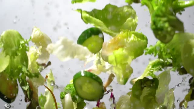 slow motion of splashing green salad flying up - vegetable stock videos & royalty-free footage