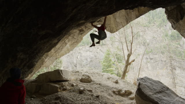 slow motion of spotter watching woman rock climbing on ceiling of cave / american fork canyon, utah, united states - braided hair stock videos and b-roll footage