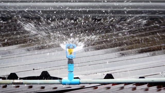 slow motion of sprinkler on roof - roof stock videos & royalty-free footage
