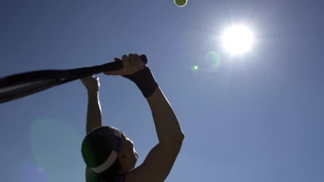 slow motion of tennis player serving ball against the sunlight - tennis stock videos & royalty-free footage