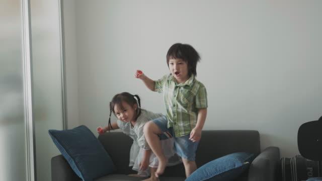 タイの男の子のスローモーションと彼の妹をジャンプし、リビング ルームに肯定的な感情を踊り始め