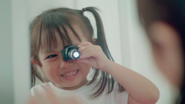 slow motion of thai cute baby girl playing camera toy in front of the mirror while smiling and laughing with positive emotion - baby girls stock videos & royalty-free footage