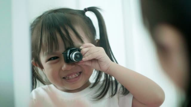 Slow motion of Thai cute baby girl playing camera toy in front of the mirror while smiling and laughing with positive emotion