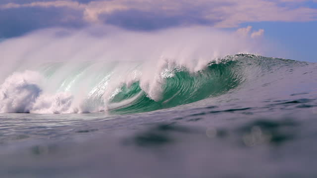 slow motion of the mist and spray rising off a crashing wave with bright blue sky and sparkling green ocean water - oahu, hawaii - wasserrand stock-videos und b-roll-filmmaterial