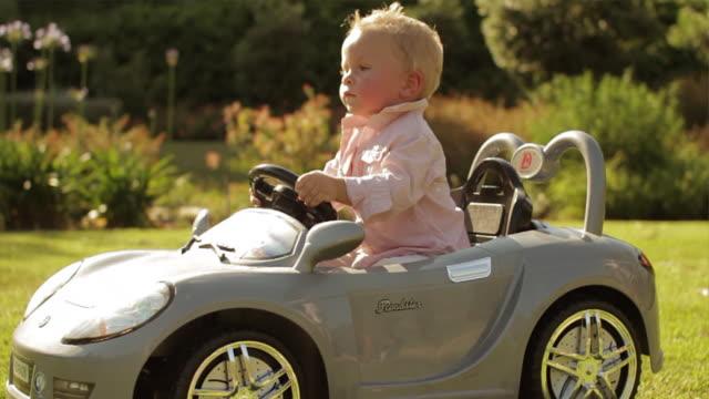 slow motion of toddler playing in toy car/benhavis, marbella region, spain - 男の赤ちゃん一人点の映像素材/bロール