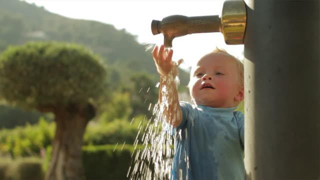 vídeos de stock e filmes b-roll de slow motion of toddler playing with water at playground/benhavis, marbella region, spain - só um bebé menino