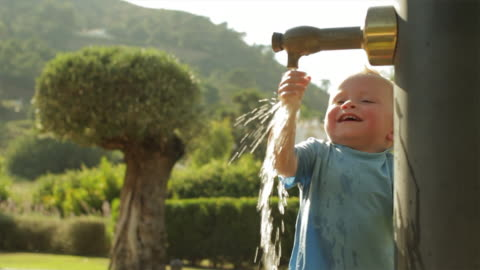 slow motion of toddler playing with water at playground/benhavis, marbella region, spain - one baby boy only stock videos & royalty-free footage