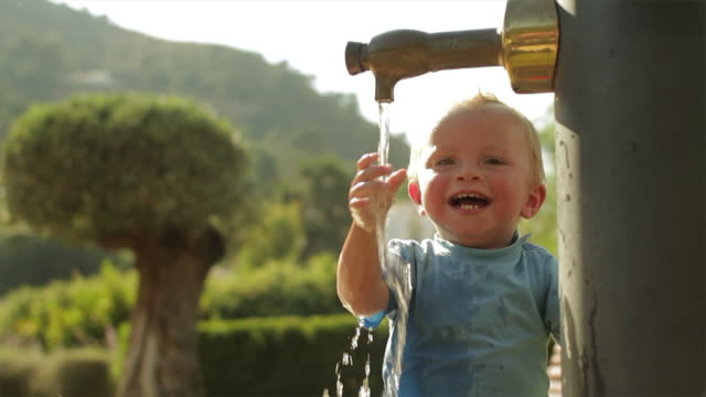vídeos de stock, filmes e b-roll de slow motion of toddler playing with water at playground/benhavis, marbella region, spain - só um bebê menino