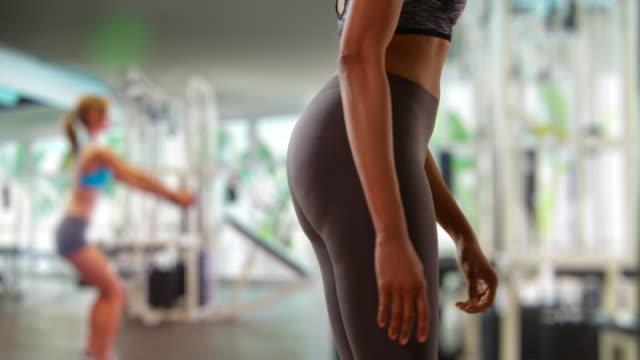 slow motion of toned black female stretching legs at gym - 柔軟性点の映像素材/bロール