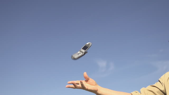 slow motion of tossing cellphone - 投げる点の映像素材/bロール