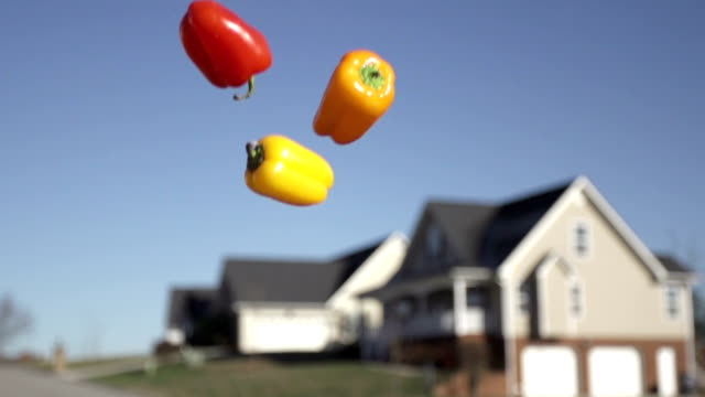 slow motion of tossing food into sky with blurred house in the background - オレンジピーマン点の映像素材/bロール