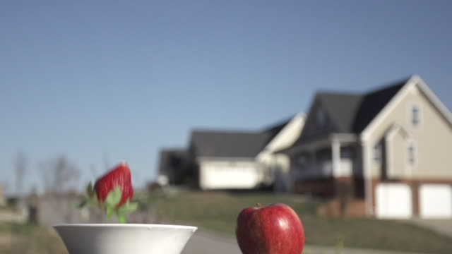 Slow Motion of Tossing Strawberry Into Sky With Blurred House in The Background