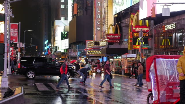 slow motion of tourist, kids walking and tricycle in times square, new york city at night - ペディキャブ点の映像素材/bロール