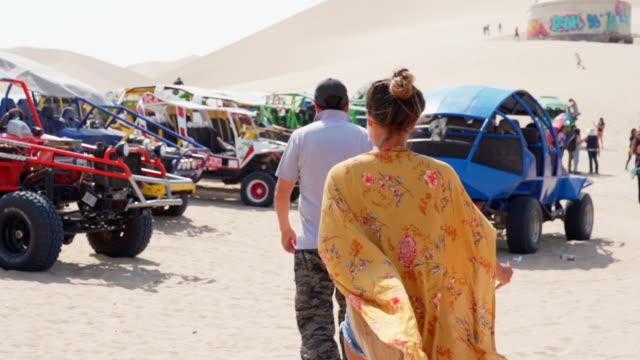 slow motion of tourists walking towards dune buggies at desert, woman and man are moving towards safari vehicles - huacachina, peru - film festival stock videos & royalty-free footage