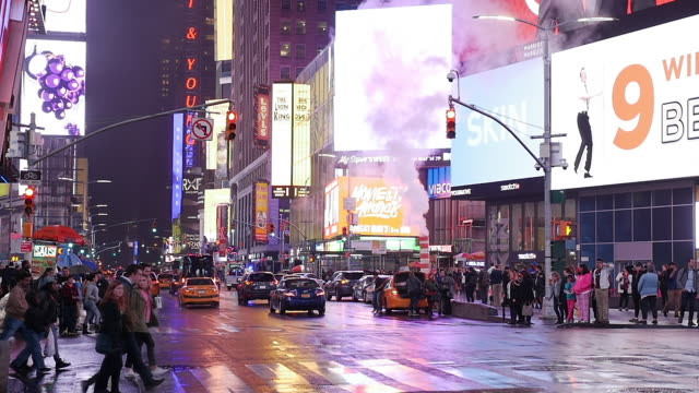 Slow motion of traffic and tourists walking in a rainy night in New York City Manhattan's Times Square