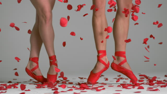 slow motion of two Ballerinas feet and legs Performing with red confetti floating down
