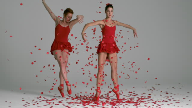 slow motion of two Ballerinas performing in red with red confetti floating down