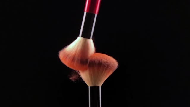 Slow motion of Two make-up brush spreading.