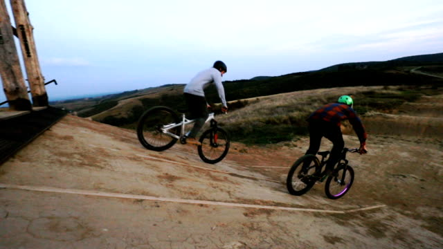 Slow motion of two men on mountain bicycles starting a race and riding over dirt hills.