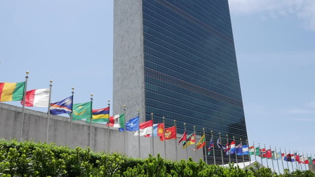 slow motion of un flags in wind in new york city - united nations building stock videos and b-roll footage
