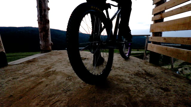 Slow motion of unrecognizable cyclist spinning back wheel of his mountain bicycle on dirt ground.