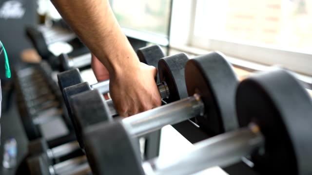 slow-motion von unkenntlich mann unter gewichte aus dem rack - gewichtstraining stock-videos und b-roll-filmmaterial