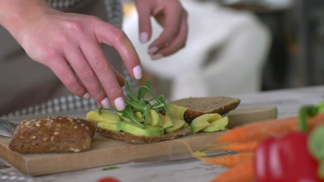 slow motion of unrecognizable young female making an avocado sandwich - recipe stock videos & royalty-free footage