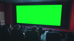 Slow motion of viewers clapping hands looking at green chroma key cinema screen