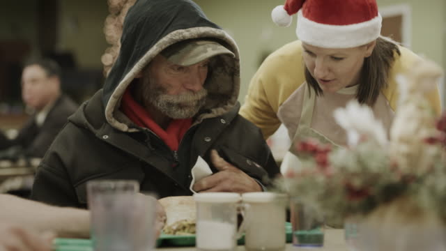 slow motion of volunteer wearing santa hat talking with man eating meal in homeless shelter / provo, utah, united states - homeless shelter stock videos & royalty-free footage